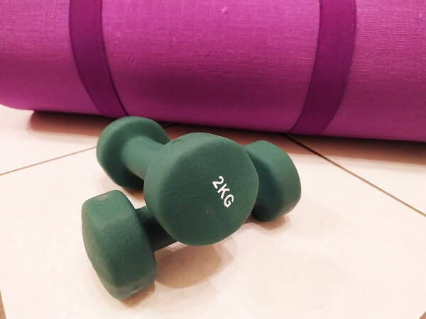 Attrezzi per fare ginnastica a casa: sul pavimento ci sono un tappetino fucsia arrotolato e due pesetti da due chili l'uno color verde bosco pronti per essere usati