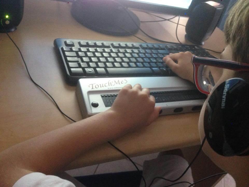 Un bambino non vedente scrive al computer. E' inquadrato di spalle, con mani sulla tastiera