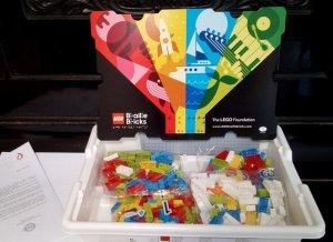 La confezione dei Lego Braille con il logo del progetto su sfondo nero e con quattro petali colorati di rosa, giallo, azzurro e verde, che contengono disegni con sport e giochi per bambini