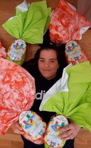 Federica, una delle ragazze che sta svolgendo il tirocinio di inclusione sociale posa sdraiata a terra e circondata da uova di Pasqua avvolte in confezioni colorate di verde e di rosa