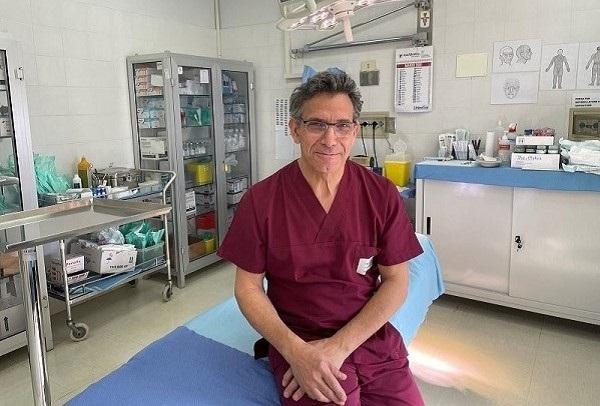 una bella immagine del dottor Alfredo Giacchetti nel suo studio medico. E' appoggiato a un lettino da visita e indossa un camice bordò e un sorriso rassicurante.