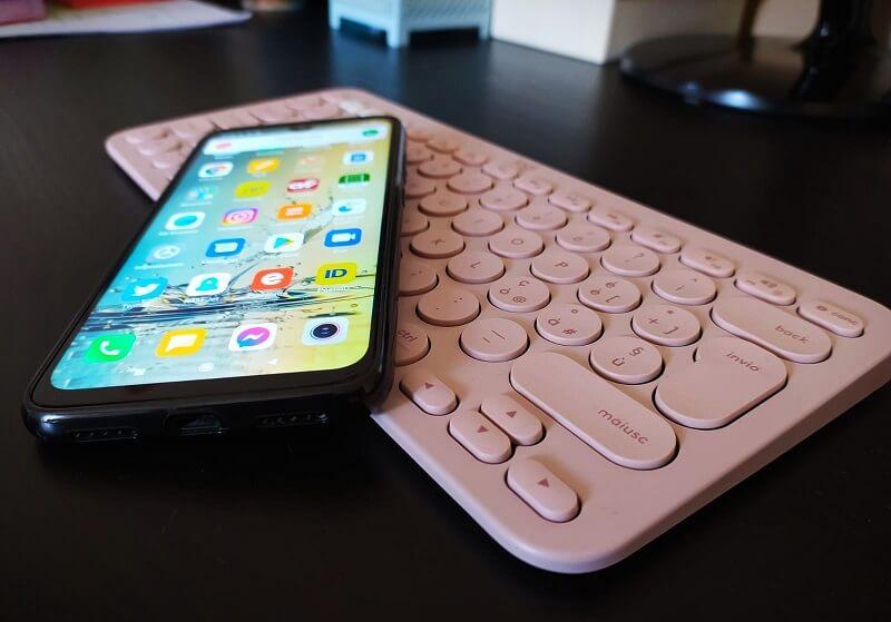 Una tastiera rosa cipria e un cellulare acceso con le icone delle diverse applicazioni in evidenza sono appoggiati su un piano nero
