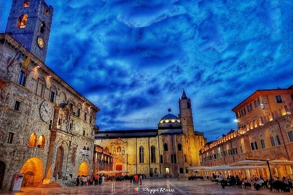 La splendida piazza del Popolo di Ascoli Piceno con i colori del tramonto. Il cielo ha sfumature blu e azzurre e le prime luci dei lampioni illuminano i palazzi storici. Il bellissimo scatto che rappresenta la città di Ascoli Piceno ci è stato donato da Peppe Rossi, fotografo per passione