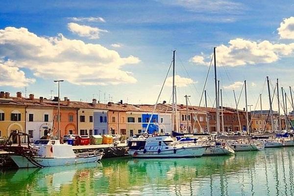 Una bellissima immagine di Pesaro scattata dalla presidente Uici Maria Mencarini. Il porto canale è inondato di colori, dall'azzurro del cielo ai riflessi verdi dell'acqua, alle case che si affacciano sul canale.