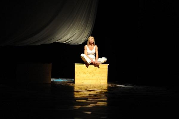 Stefania Terrè recita sul palcoscenico di un teatro. Su sfondo nero, è seduta su un cubo color legno illuminato da un faro a occhio di bue. Indossa pantaloni chiari e una canotta bianca. E' seduta con le gambe incrociate, stile indiano.