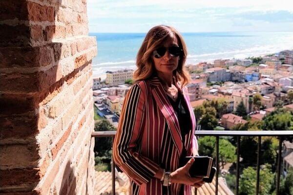 Una bella immagine della dottoressa Emanuela Storani sul belvedere di Grottammare. Indossa una elegante giacca a strisce verticali rosse, bianche e nere. Ha in mano una pochette nera e sulla sfondo il panorama della costa visto dall'alto