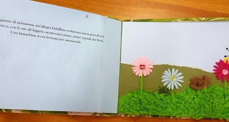 Una fiaba su un libro tattile: a sinistra la pagina con il testo. A destra le illustrazioni tattili con un prato fiorito, fiori e una farfalla colorata