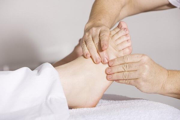 Le mani di un fisioterapista massaggiano il piede di una paziente distesa sul lettino