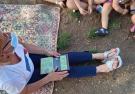 Una lettrice è seduta per terra, su una coperta colorata e ha sulle gambe il libro che sta leggendo. Intorno a lei si vedono le gambine dei bimbi seduti in terra che la ascoltano