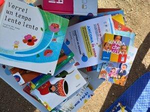 Una serie di libri con copertine colorate sono sparsi su un piano color legno, pronti per essere letti