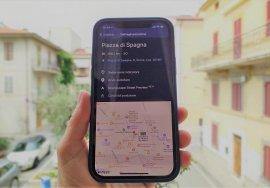 Una mano regge il cellulare collegato all'applicazione soundscape che mostra il percorso per arrivare a Piazza del Popolo, a Roma. Sullo sfondo c'è il panorama della piazza di un paese