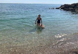 Stefania e il suo Italo al mare. Stanno uscendo dall'acqua dopo aver fatto il bagno. Stefania indossa un costume nero, tiene Italo con una mano e l'acqua intorno è cristallina