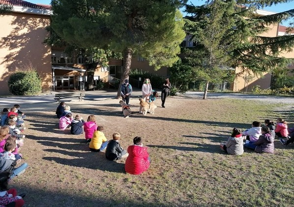 I bambini della scuola elementare di Macerata sono seduti in circoli nel giardino dell'Istituto, in una bella giornata di sole. Stefania Terrè, il suo Italo e le insegnanti sono in piedi davanti ai piccoli