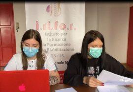 Sara e Noemi al lavoro nella sede Irifor-Uici Marche. Sono sedute davanti a una scrivania. Sara è al computer e Noemi ha in mano alcuni fogli.