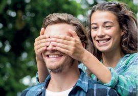 Una ragazza copre gli occhi a un ragazzo abbracciandolo dalle spalle. Sorridono entrambi. Lei indossa una camicetta verde acqua, lui una camicia azzurra e blu a scacchi aperta su una maglietta bianca.