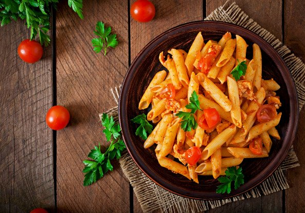 Un bel piatto di pasta tonno, pomodorini e prezzemolo, su una tavola rustica color mattone e con pomodorini e foglioline di prezzemolo tutto intorno al piatto