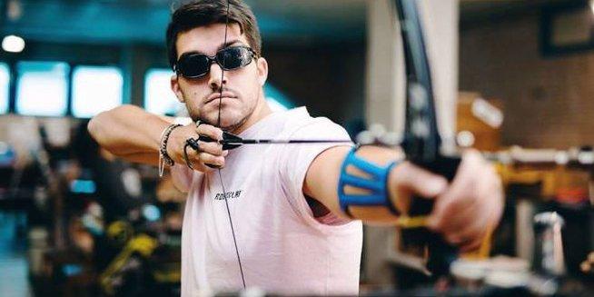 Una bella immagine di Giordano Cardellini che tira con l'arco. Imbraccia l'arco e lo tende, un momento prima di lanciare la freccia. Indossa una maglia rosa, intorno c'è il pubblico che assiste alla gara