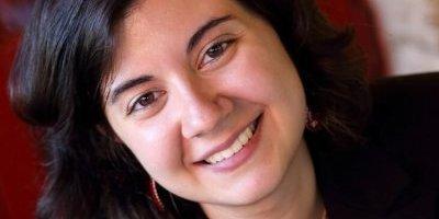 Un bel primo piano dell'archeologa Giulia Sinopoli che indossa una giacca nera su vestito rosso