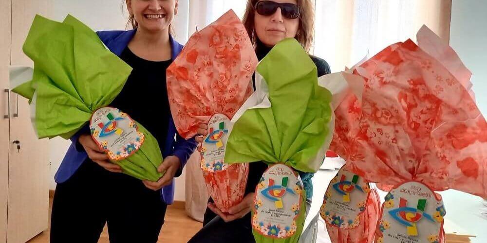 Nella foto, da destra, la presidente Uici di Ascoli e Fermo, Gigliola Chiappini e il segretario territoriale, Margherita Anselmi, ci sorridono e hanno in mano un uovo di Pasqua. Altre uova sono sistemate sul tavolo in primo piano. Margherita è in piedi. Gigliola è appoggiata al tavolo. Le uova di cioccolato sono avvolte in confezioni verde pastello e rosa salmone. In evidenza, su ogni confezione, il logo dell'Uici.